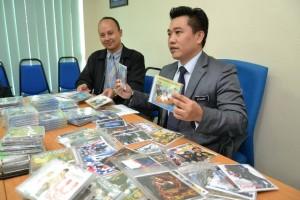 砂贸消局局长斯丹利陈(右)及执法组官员亚历山大展示充公的盗版光碟。