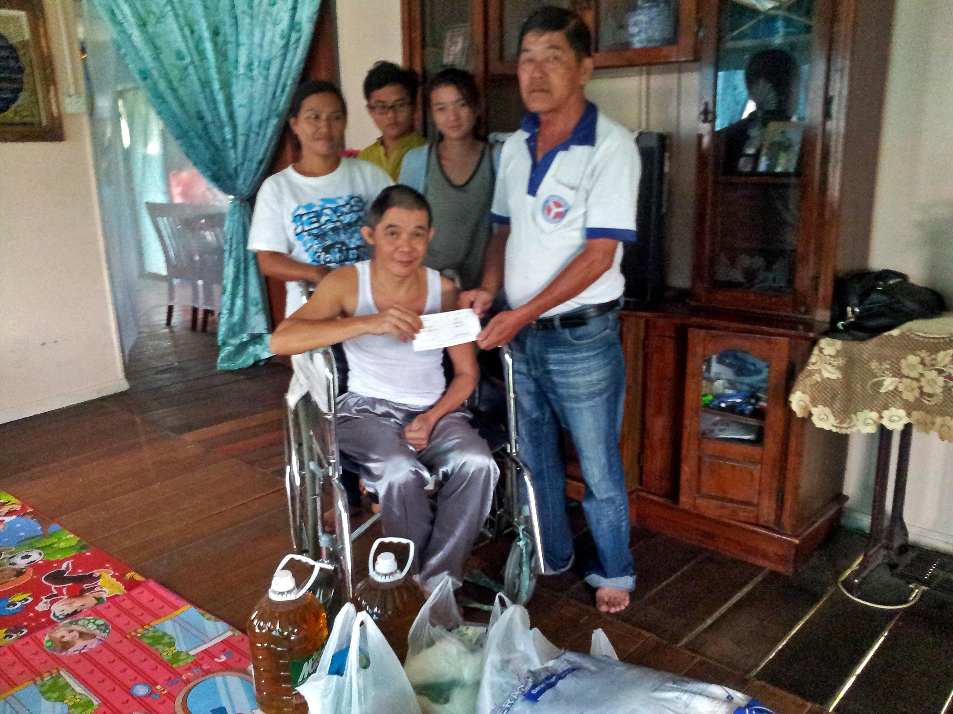 查法里代表家人从前同事代表杨木和手中接过救济品时摄。