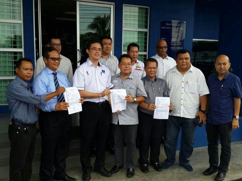 4个砂州国阵成员党青年团代表展示报案纸。