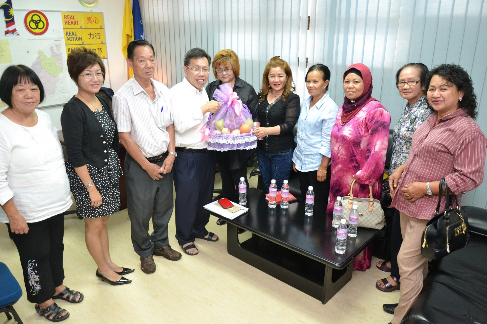 Serian welfare association chairperson Wisdon Hoan (left fifth) giving a souvenir to Datuk Sim.