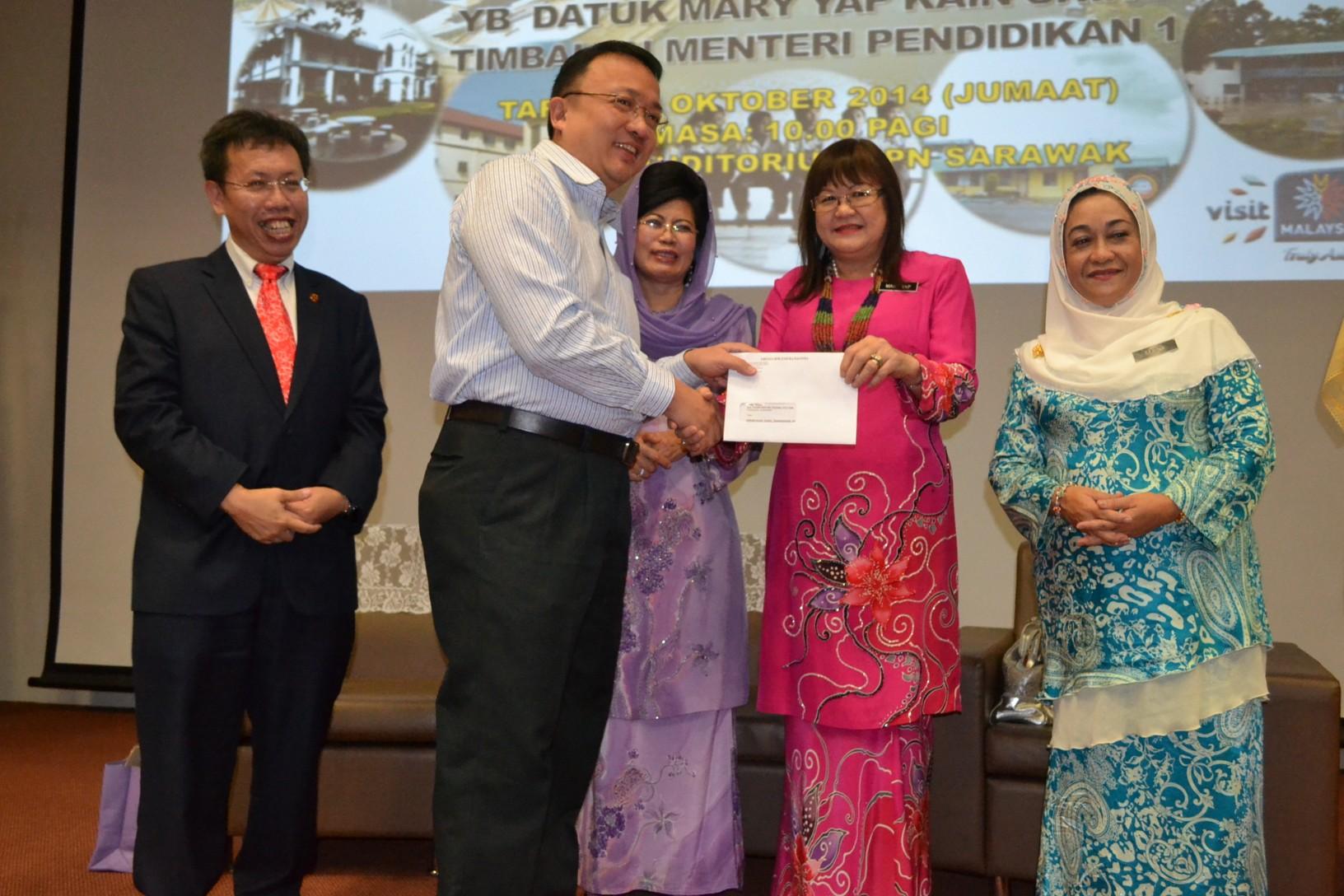 副教育部长叶娟呈颁发模拟支票予其中一间受惠学校代表蔡文铎,左一图片