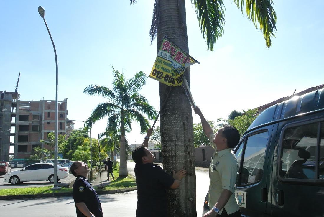 叶耀星(右一)与巴达旺市议会执法组拆除住宅区内非法借贷广告布条。