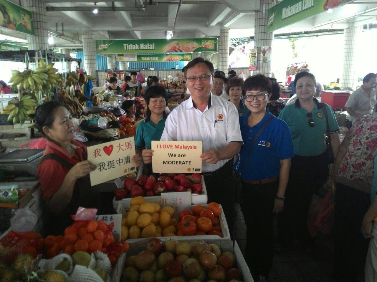 砂人联党哥打圣淘沙支部主席罗克强及中央妇女组顾问郑荔嫔与民众一起支持中庸。