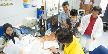 Photo shows SUPP PCB Chief Wilfred Yap together with the father and his intellectually challenged son at the National Registration Department, Kuching