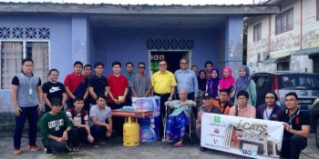 YB. Cr. Ir. Lo Khere Chiang (in yellow shirt) presenting a new gas stove, gas cylinder and mattress to En Tekong bin Darmo (sitting in wheelchair)
