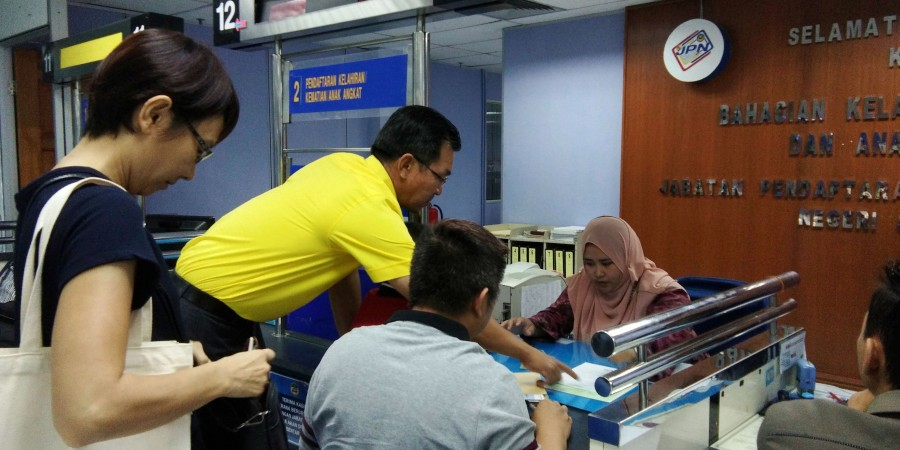 SUPP PCB Chief Wilfred Yap assisting the anxious father from 7th Mile at Jabatan Pendaftaran Negara, Simpang Tiga  to submit his application to register the  Certificate of Adoption of the child issued by Kuching District Office.