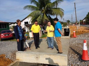 Dr. Sim and Lo seeing the progress of the drain