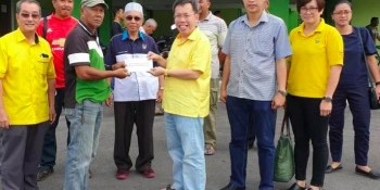 Dr. Sim giving the grant and RTP to representatives of the kampong
