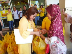 Datin Enn Ong giving the goodies to a mother.