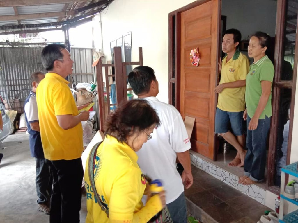 Yap together with SUPP members at one of the houses visited at Stampin Resettlement Scheme to explain and hand over brochures on the procedure to apply for refund of land premium.