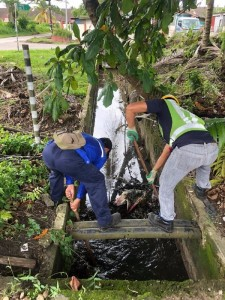 Public Works Department (JKR) workers clearing the drainage system at the inundated road.